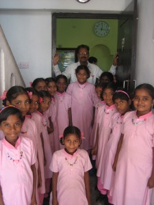 The girls standing in the school's hallway, showing of their new necklaces.